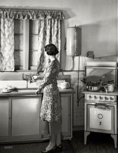 "New Zealand circa 1930s. ""Model at sink in kitchen equipped with Atlas electric stove and Zip water heater."""