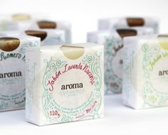"""Aroma by Claudio Limon: """"For this project the client asked me to create an affordable package where you could see, and smell the product. It also needed to be easy to package by hand and original... I... created a square, waxed paper wrapper. An oval die cut was added to allow the consumer to see and smell the product."""" 