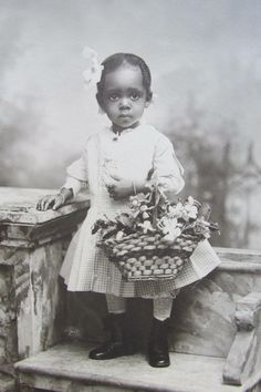 A beautiful little girl holding flowers in a basket, 1890's.