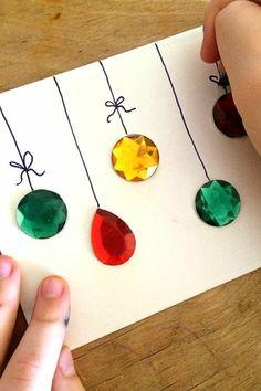 activite manuelle noel sur du carton blanc, avec des éléments décoratifs autocollants en vert, jaune et rouge, qui imitent les boules sur le sapin