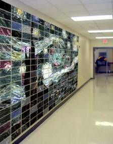 """Students create a master work mural from matrix grid. Prior to this lesson, students have had color theory and know all of the color plans and what colors work best to match value scale (high key and low key colors). Lesson builds a sense of """"community"""" - all parts are needed to make a whole. All students' work is exhibited. This would make a nice display for open house/parent night - or for a wall display announcing up coming art show (later in the year)."""