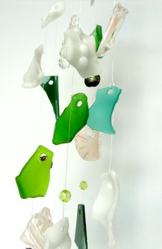 Glass wind chime in shades of green, pink & white. Shades of blue, green, pink and white tumbled glass and Lampwork glass beads were combined to create this glass wind chime. The wind chime with contrasting colors reflects the light beautifully. The white glass has raised hobnails and there are a few pieces of stained tumbled glass that create a lovely tinkling sound. The hardware is powder coated in Wrinkle white to create a beautiful finish and prevent rust. The wind chime process...