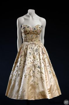 Christian Dior Evening Dress 1951 from ivory silk satin with polychrome. Flowers were a consistent theme in Dior's work, often represented by the silhouette of a dress or a floral-patterned fabric. The embroidered flowers on this dress appear to be growing around the wearer's body: in full bloom at the top of the bodice and trailing off as vines near the hem. Dior's expression of the overtly feminine silhouette was embraced by magazines like Vogue, whose Paris fashion editor owned this…