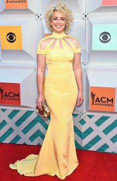 CAMARON OCHS  selects a not-so-mellow-yellow Christian Siriano gown with a laser-cut neckline that plays up her Goldilocks curls, plus an Emm Kuo clutch.