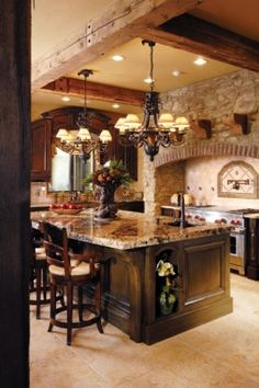 The space features dark-stained, heavily distressed cabinetry, much of which was designed to look like pieces of furniture. The room features a massive island with a chiseled-edge granite top filled with creams, blacks and rusts.