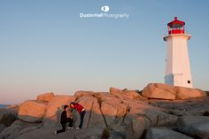 Best proposal ever, Dustin Hall proposing at Peggy's Cove with the lighthouse at sunrise.  Beautiful Photo