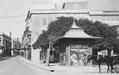 """Old Malta -A Route Bus heads down deserted Tower Street, Sliema towards the Landing Stage, known as """"The Ferries"""" as a Horse with Karozzin waits for trade outside the Majestic Theatre. A poster on the kiosk for The Gaiety Theatre promotes the film Naughty Marietta starring Jeanette MacDonald and Nelson Eddy. This film was a hit when released in 1935. The Magic Kiosk restaurant now stands on this corner, maybe named after this very kiosk."""
