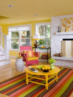 Juicy Color Scheme  A few cans of paint give this living room a drenching in juicy color. White paint updates the fireplace, while citrus yellow coats the walls and ceiling for a warm and happy vibe. Bright golden paint enlivens an old coffee table, and an old wicker chair gets a new look with watermelon-pink paint. The color scheme combines in a striped rug that also introduces a jolt of lime green