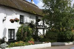The 13th Century thatched Coach and Horses Inn at Buckland Brewer, North Devon, England, UK.