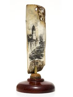 """Safe Arrival"" Black and white scrimshaw on ancient walrus tusk ivory artifact by Gerry Dupont. After a long and successful voyage, a full rigged ship returns to port. Very nice detail by Dupont in this one. Interesting artifact as well. Note the tiny hole in the top of the ivory. Have no idea how it was used, but that only adds to the allure of this one. Size: 1 3/4""Diameter x 4""H Price: $195.00 -- on ScrimshawGallery.com"
