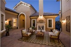 A private courtyard with an outdoor fireplace makes an inviting space to entertain or just relax. The Tuscany Model by Taylor Morrison. Lutz, FL.