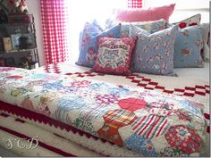 Love the scrappy snowball quilt on the foot of the bed