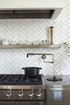 White herringbone splashback tile. A black pot fromCrane Cookware, perched beneath a pot-filler faucet. Clare and Harrison Mill Valley Kitchen Remodel Photo by Andres Gonzalez