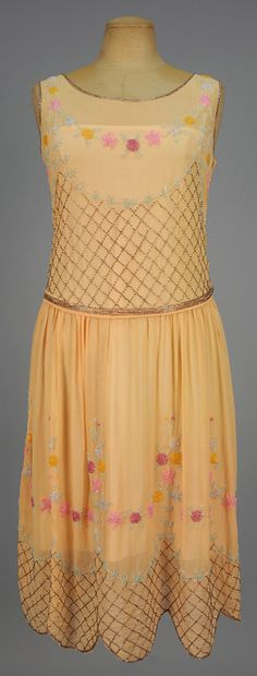 BEADED CHIFFON DANCE DRESS, 1920s. Sleeveless apricot silk having a lattice of crystal bugle beads and pastel floral swags, dropped waist, gathered skirt with scalloped hem. B-34, low W-32, L-43. (Two 2-inch piece of beaded lattice missing from bodice, other minor bead loss) good.