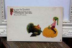 Antique Thanksgiving Postcard with a little boy or elf sitting on a pumpkin talking with a turkey by S. Bergman