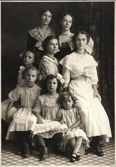 A portrait of a Mother and her seven daughters don't often see people in these old photos that are beautiful by modern standards. These girls are unusually beautiful. Hard to guess which one is the mother.