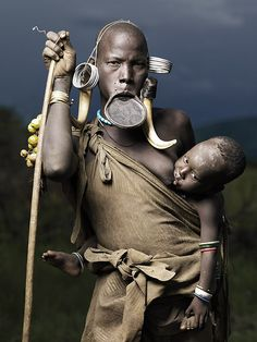 Portrait of Nadogomi and Bardomoye by Joey L.  - Nadogomi is a mother of 5 children. The boy in the picture's name is Bardomoye.  The clay disk inserted into a woman's lower lip is a Mursi tribe tradition.