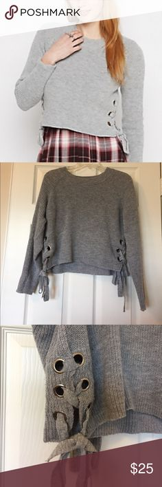 Grey Side Lace Up Crop Top Sweater NWOT. Light Grey Sweater material. High/Low Crop top style but may hit just above waist on some frames. Left/Right Side lace tie up. Silver metal loops. Rue 21 Sweaters