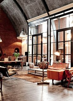 Loft With High Ceilings    Wood floors and mid-century modern furniture play up warm brick.