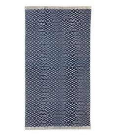 Dark blue/natural white. Rectangular rug in woven cotton fabric with a printed pattern at front.