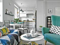 Mała kuchnia (ok. 5 m kw.) jest połączona z pokojem dziennym. Umowną granicę wyznacza stół, przy którym stoją krzesła ogrodowe z IKEA - mają ażurową konstrukcję, dzięki czemu wyglądają bardzo lekko. Poduszka na fotelu powstała w pracowni gospodyni, z niej pochodzi też tkanina, którą został obity stary puf.