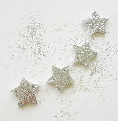 """twinkle twinkle little star - 4 star garland  '""""a falling star was caught & star twinkles were sprinkled over the mud to add delight & wonder""""  each star is sprinkled with silver sprinkles to make a gorgeous sparkling star - use all four for a stunning garland to decorate your nest, or use each tag individually to tie to your gift wrap or table setting. makes a gorgeous gift for a new born or christening or a secret santa gift at christmas.  each star measures approx 4cm  each tag ..."""