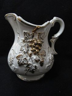 This is a ceramic Pitcher Vase, Planter. Very detailed gold fruit and leaves in a 3 dimensions.  Gold and White. Has gold grapes leaves, and vines on the front. Very ornate.5 inches long, 4 inches wide and 5 1/2 inches tall. Perfect for cut flowers, silk flowers or a small plant. Could be used as a cream pitcher on your dinning table.        To view other planter/vase in my shop:    https://www.etsy.com/shop/DigginThruTheAttic/edit?ref=edit_trust_header§ion_id=15989016   Shop this product…