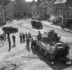 A Sherman Firefly and other vehicles in the village of Putanges, 20 August 1944.