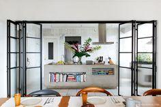 Cozinha integrada com portas de serralheria e bancada de concreto