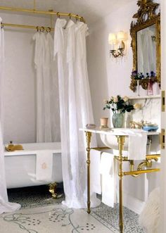 Pretty Feminine Bathroom with Gold Accents, Marble Sink, Claw-foot Tub and Double Shower Curtains.