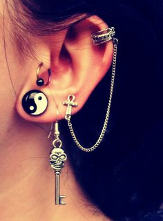 Obsessed with the yin-yang gauge. Also depicted: tragus, triple lobe piercings, and cartilage piercing