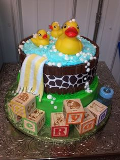 "Rubber Ducky baby shower cake. 8 inch and 10 inch stacked cake. The ""barrel"" is kit kat bars turned backwards with a ribbon around them. I bought wooden blocks and spelled out the babys name. Ace Ryan."