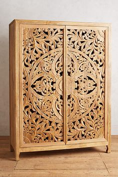 Handcarved from solid mango wood, this elegant armoire is a true work of art. Its filigree-inspired cutouts create a lively shadow play when placed near a sunny window