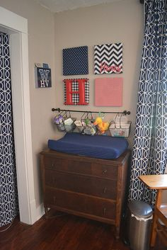 I like the idea of a towel bar or short curtain rod with baskets that have handles on them hanging over the changing table. Great storage within reach where you most need it.