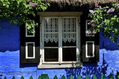 Blue cottage with wycinanki (papercut art) decorating the windows. Skansen in Maurzyce, Poland, fot. Mariusz Banaszczyk.
