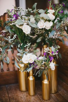 gold painted bottles, photo by Awake Photography http://ruffledblog.com/one-world-theatre-wedding #weddingideas #decor #weddingdecor