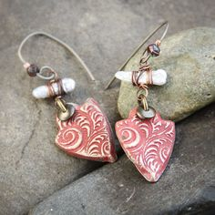 A white freshwater pearl is wirewrapped in a tribal style and paired with a handmade polymer clay shield bead in shades of deep coral and olde silver. Topped off with handmade non-allergenic Titanium earwires that hold a faceted picasso style Czech glass bead. Titanium is nickel and lead free. These earrings are as light as []