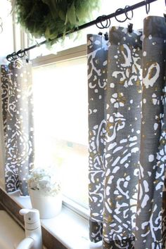 petits rideaux cuisine en gris à motifs blancs et jaunes et un petit vase rond avec hortensia blanc