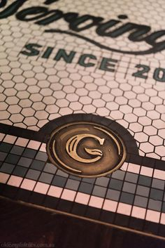 Custom mosaic logo at The Grounds of The City. Design by Acme & Co, tile supply by Olde English Tiles Bar Logo, Geometric Tiles, Lettering Design, Fine Dining, Signage, Mosaic, New Homes, English, Flooring