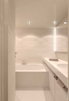 All white bathroom with mirrors and lights.