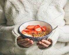 #Healthy breakfast yogurt & granola  Healthy breakfast greek yogurt granola and strawberry bowl in hands of woman wearing white loose woolen sweater selective focus. Clean eating healthy vegetarian dieting food concept
