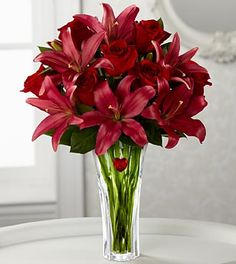 Red roses arranged amongst scarlet Asiatic Lilies