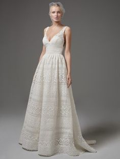 Sottero and Midgley - EVAN, This chic boho wedding dress features sheer pockets and patterns of eyelet lace, floral motifs, and scalloping in an A-line silhouette. Sheer lace straps complete the V-neckline and sexy square-back. Finished with zipper closure. Detachable tulle overskirt with lace waistband sold separately.