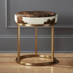 Shop hide brass stool.   Stunning brown and white hide tops a shiny brass base for a modern juxtaposition of organic and glam.  Each luxe hide is totally unique.  No two ever look the same.