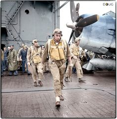 US Navy pilots, (in front) Lieutenant (jg) Henry H. Dearing of Cleveland, Ohio, Ensign Charles W. Miller of Houston, Texas and Lieutenant (jg) Bus Alder of San Mateo, California walking toward their Grumman F6F-3 'Hellcats' aboard the aircraft carrier USS Saratoga (CV-3) on the 5th November 1943.