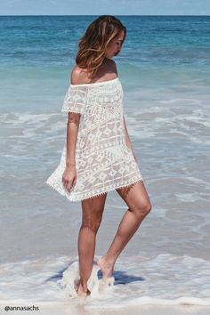 A semi-sheer crochet swim cover-up featuring an elasticized off-the-shoulder neckline, scalloped short sleeves, and a mini length.