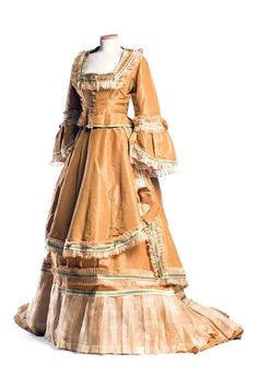 Saffron gold silk dress  Dress c. 1869, with organdy and lace edging, green and cream satin ribbons. The overskirt gathers up in to add emphasis to the back, a precursor to the bustle. This gown was worn by Frances Olmsted (later Mrs. Richard Maynard Marshall) when she attended the first St. Cecilia Ball held after the Civil War. Courtesy of The Charleston Museum.