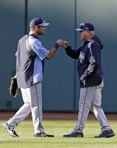 Tampa Bay Rays manager Joe Maddon, right, greets outfielder Kevin Kiermaier before the AL wild-card baseball game against the Cleveland Indi...