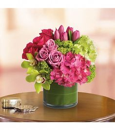A very popular arrangement we do for our clients. New Sensation is the name. Upscale and uptown. This fantastic arrangement is a beauty and a half to behold. Overflowing with gorgeous blossoms and delivered in a leaf-lined cylinder vase, it's truly a floral fantasy. Green and pink hydrangeas, green cymbidium orchids, hot pink and lavender roses, tulips and more are beautifully arranged in a large clear glass cylinder vase. T82-3A