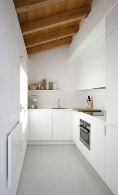 Small white kitchen with wooden ceiling beams. Villa Piedad by Marta Badiola. Photo by Francisco Berreteaga